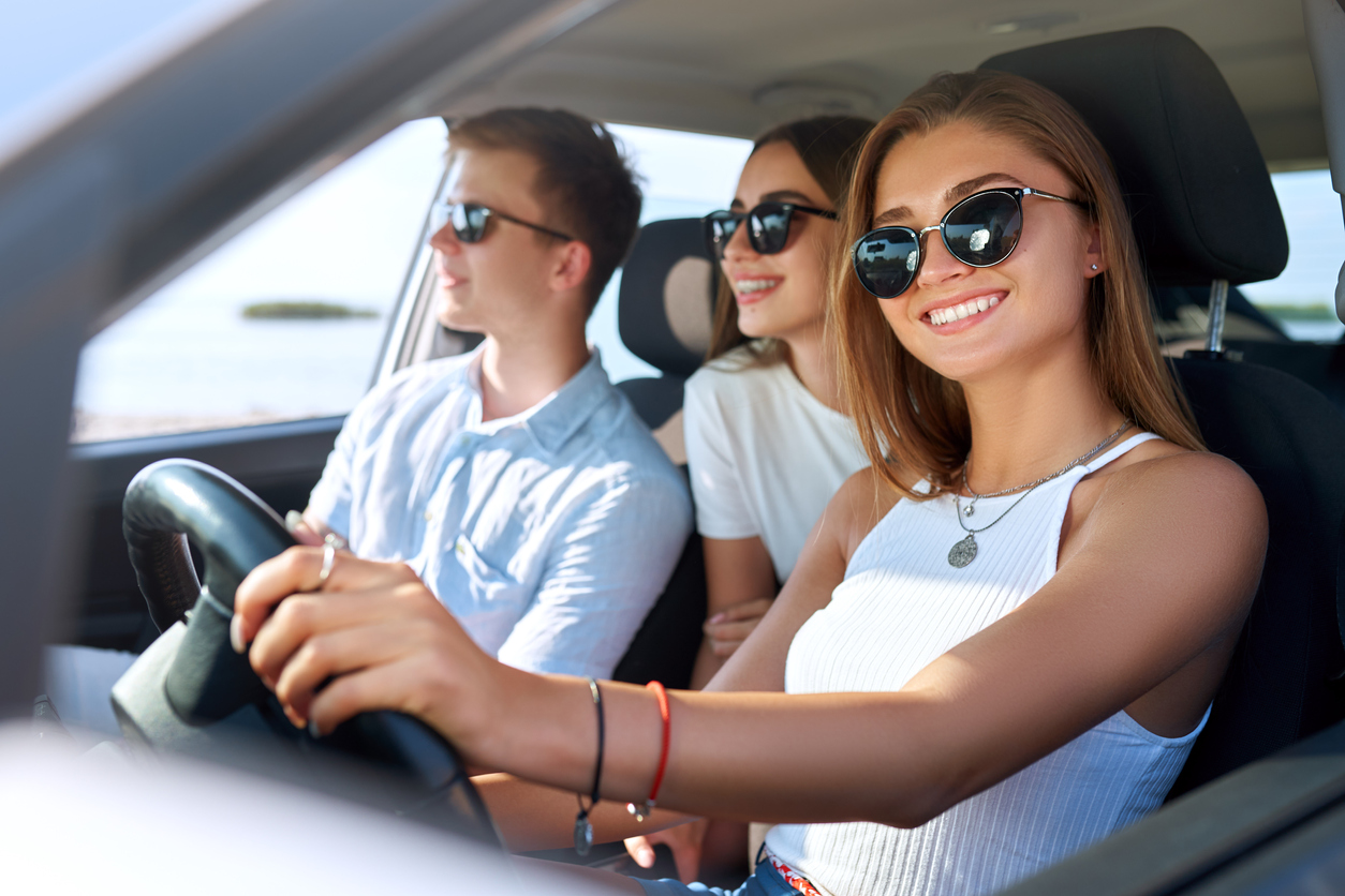 Group of friends rented a car on summer road trip and arrived to the sea beach. Girl having fun with friends in vehicle. Woman in glasses learned driving and got a driver license. Travel lifestyle